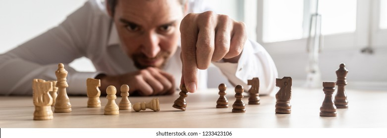 Businessman brainstorming as he creates business strategy by placing black and white chess pieces on office desk.