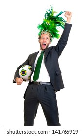 Businessman with brazilian soccer ball and Carnaval head dress isolated in white
