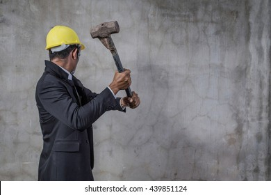 businessman breaking trough a old wall
