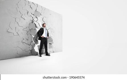 businessman is breaking trough a wall