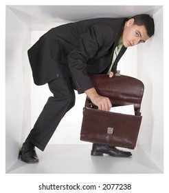 businessman with briefcase in the cramped white cube