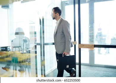 Businessman with briefcase entering cafe