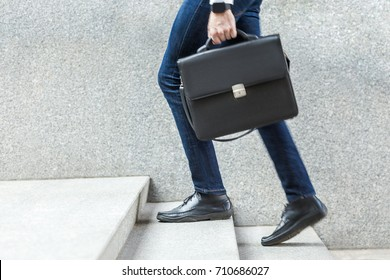 Businessman with briefcase in hand walking up on stairs. Outdoor shoot