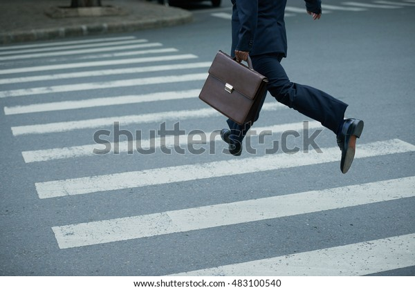 Businessman with briefcase hurry to cross the road