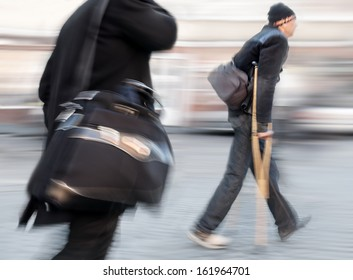 Businessman with a briefcase and a man on crutches walk along a city street. Intentional motion blur
