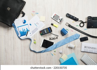Businessman briefcase with paperwork and accessories on the floor, business failure concept.