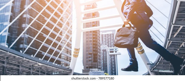 Businessman with a briefcase running fast in a city street on a background rush hour