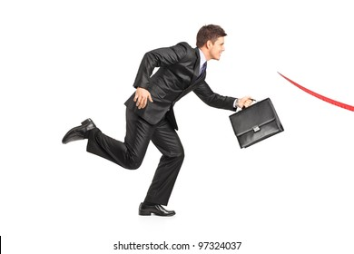 Businessman with a briefcase running towards a finish line isolated on white background