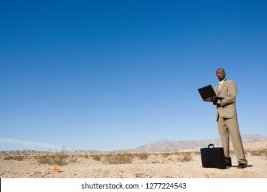 Businessman with briefcase using laptop computer in desert