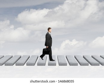 businessman with briefcase walking on sky
