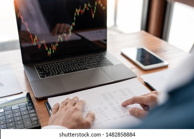businessman or broker looking at computer laptop analysing about stock market invest trading stocks graph analysis candle line in office room.