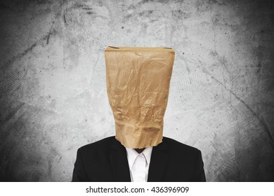 Businessman with brown paper bag on head, on dark concrete texture background