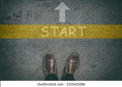 Businessman with brown shoes standing at  Start and forward direction path of arrow sign. Start to success concept. Above view feet of career businessman begin walking to arrow on asphalt.