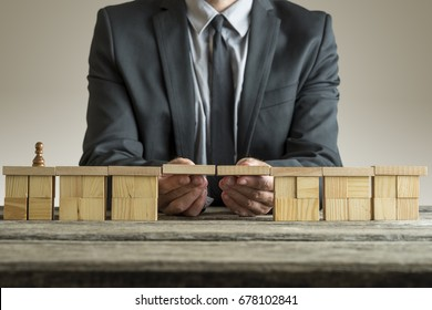 Businessman building bridge with wooden block to span a gap for chess piece pawn, conceptual image.