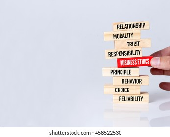Businessman Building BUSINESS ETHICS Concept with Wooden Blocks