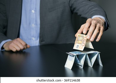 businessman building financial pyramid from euro money