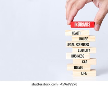 Businessman Building INSURANCE concept with Wooden Blocks