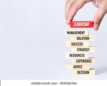Businessman Building LEADERSHIP concept with Wooden Blocks