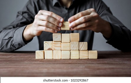 Businessman building a pyramid of wood blocks. Concept of business hierarchy and business strategy.