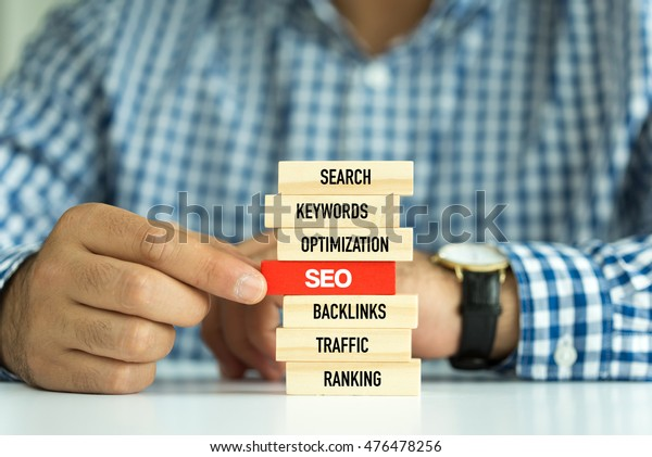 Businessman Building SEO concept with Wooden Blocks