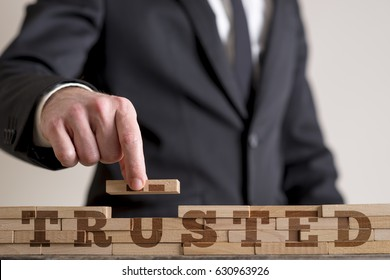 Businessman building a structure of wooden dominos while assembling word Trusted.