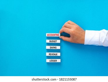 Businessman building wooden blooks with text. Concept of Accounting with basic links.