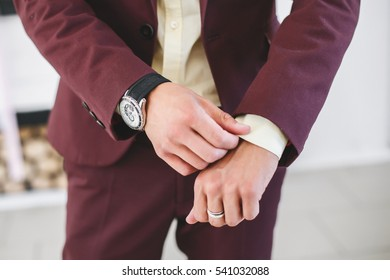 Businessman in burgundy suit with wristwatches