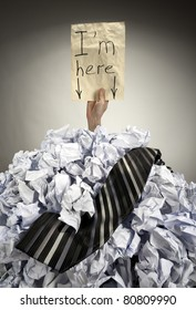 Businessman buried in big heap of crumpled papers