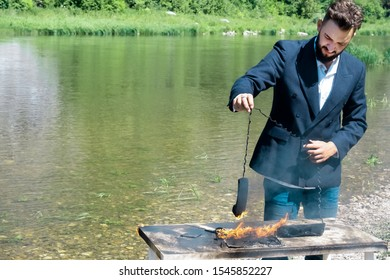 Businessman burned office equipment outdoors during the vacation. The concept of hateful work. Destruction of digital data or non-compliance with safety precautions. A laptop and a phone burned out on