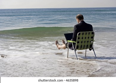 Businessman, in business clothes, under a colored umbrella at the beach, sat with his legs up in the air as the waves crash around him