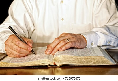 A businessman or business executive in a white, long-sleeved shirt takes time out of his day to study the Holy Bible.