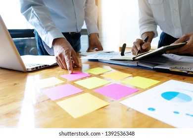 Businessman in business meeting businessman and businesswoman work on the table have graph chart and color notepad  paper