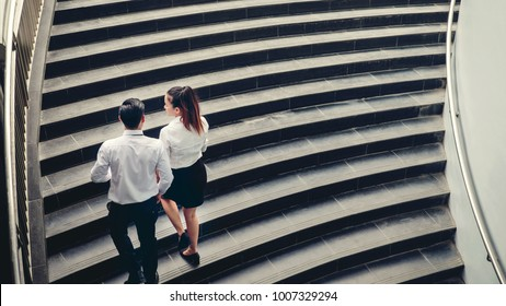 Businessman and Business woman go up the stairs Success concept