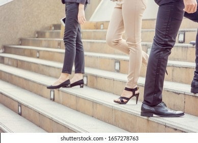Businessman and Business woman walking up stairs with smartphone outside office