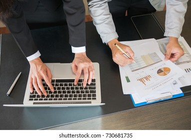 Businessman and businesswoman analysis data by paperwork and laptop computer in office