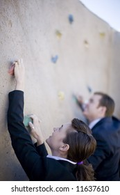 Businessman and businesswoman climb the same wall