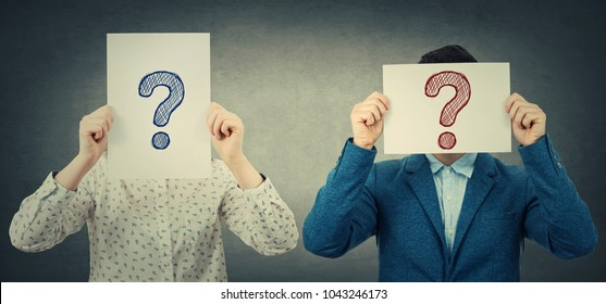 Businessman and businesswoman covering their faces using white paper sheets with drawn question marks, like a mask, for hiding identity. Isolated gray wall background.