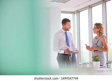 Businessman and businesswoman discussing at desk in new office
