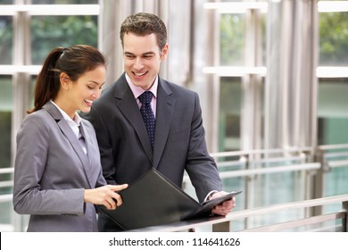 Businessman And Businesswoman Discussing Document Outside Office