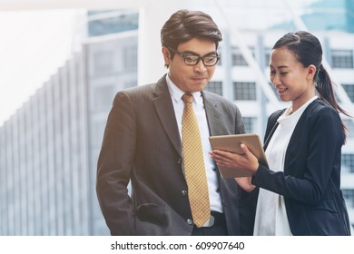 Businessman and businesswoman discussion on business issue on tablet computer with city buildings background.