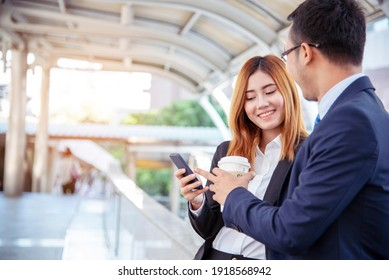 Businessman Businesswoman drinking coffee in town using smartphone outside office modern city. Hands holding take away coffee cup and smart phone talking together Business partner with cup of coffee