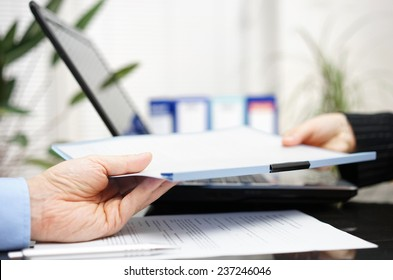 businessman and businesswoman are exchanging document or contract