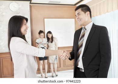 Businessman and businesswoman hand shake in the office with other business people on background