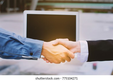 Businessman and businesswoman hands shake with computer laptop at outdoor. shaking hand for business deal complete. teamwork shake hands partnership concept. Success concept. leadership concept.