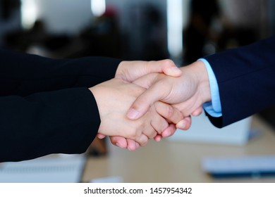 Businessman and businesswoman handshake at partnership corporate meeting, Close up of business corporate partnership handshake at meeting team to collaboration company, success in co-working business