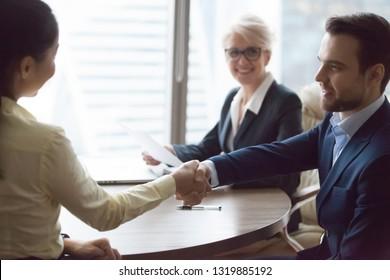Businessman and businesswoman handshaking at group meeting, happy hr manager welcoming applicant at job interview hiring successful candidate, satisfied boss rewarding thanking employee shaking hands