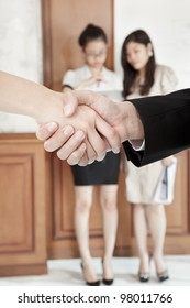 Businessman and businesswoman handshaking in the office with other people o background