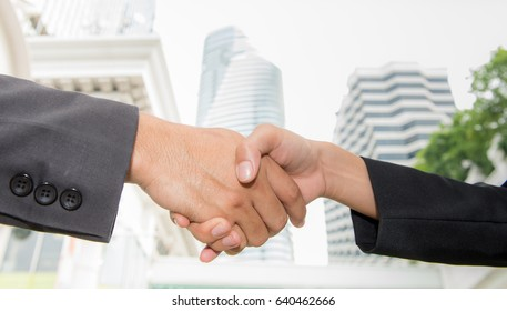 Businessman and businesswoman handshaking on building background, Business handshake with modern office skyscraper