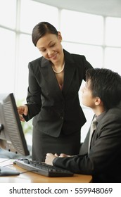 Businessman and businesswoman having a discussion, desktop computer on table in front of them