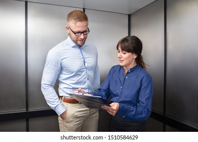Businessman And Businesswoman Having Discussion On Business Issue Over Clipboard In Elevator